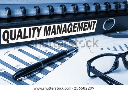 quality management label on business document folder - stock photo