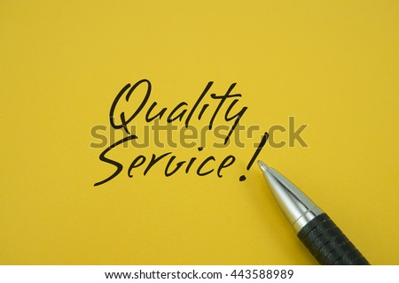 Quality Service! note with pen on yellow background