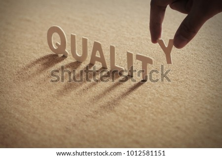 QUALITY wood word on compressed or corkboard with human's finger at T letter.