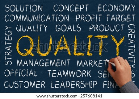 Quality word cloud is written on blue chalkboard by the hand of a businessman. - stock photo