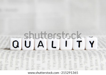 Quality word on white cube - stock photo