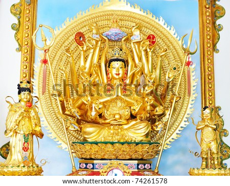 Quan Yin - Buddhist Goddess of mercy - statue isolated on gold - stock photo