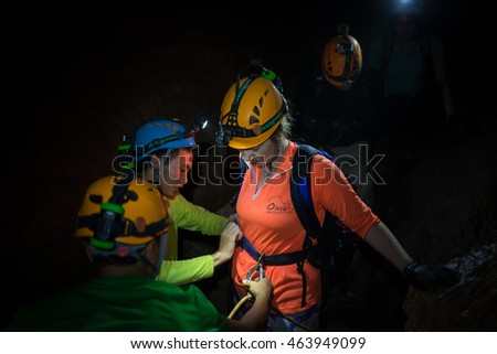 Quang Binh, Vietnam - June 20, 2016: People help each others to tighten rock climbing equipments with rope, hook, belt in dark cave in Son Dong, the largest cave in the world
