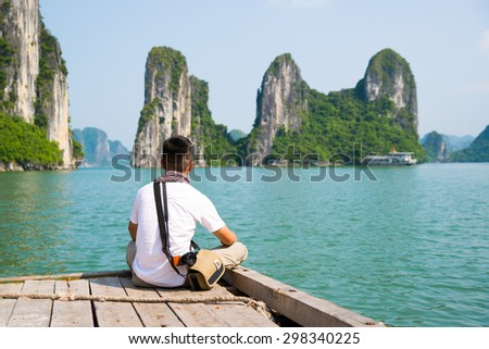 QUANGNINH, VIETNAM, July 12, 2015. Young man travel in Halong bay. Halongbay is World Natural Heritage of Quang Ninh, Vietnam.