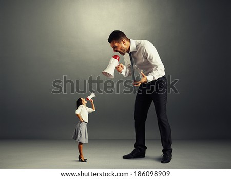 quarrel between small woman and big man over dark background - stock photo
