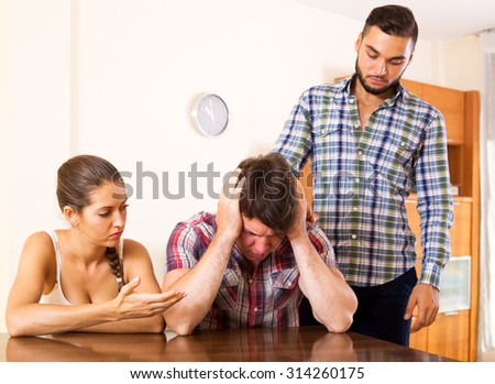 Quarrel in young polygamous family indoors. Focus in the couple - stock photo