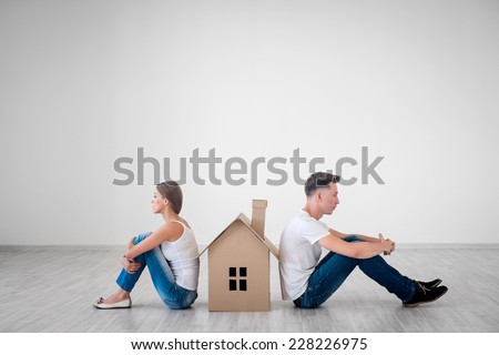 Quarreled couple with cardboard house - stock photo
