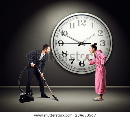 quarrelsome wife screaming at smiley husband with vacuum cleaner. photo in dark room with big clock on the wall - stock photo