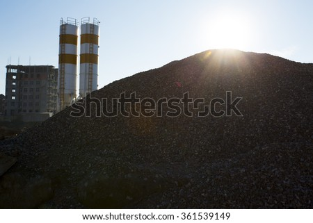 Quarry crusher plant in sand and gravel production. Cement production factory on mining quarry. Conveyor belt of heavy machinery loads stones and gravel. Construction works, machinery factory - stock photo