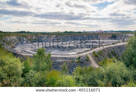 Quarry for gravel extraction on a background of blue clouds - stock photo