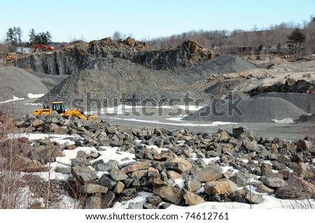 Quarry on sunny day with machinery in background - stock photo