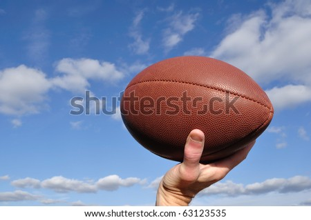 Quarterback Throwing an American Football Against a Blue Sky - stock photo