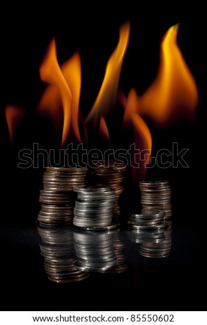 Quarters, dimes, nickels, and pennies in stacks on fire. - stock photo