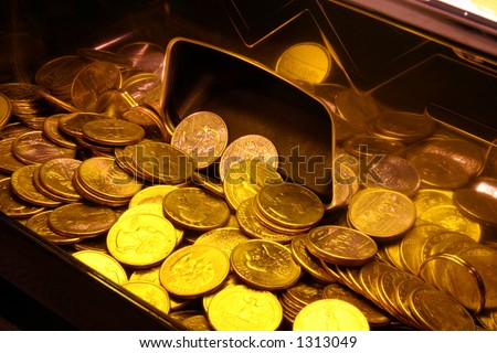 Quarters in a slot machine tray with yellow lighting - stock photo