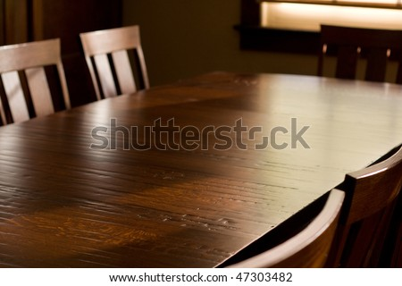 Quartersawn white oak table with distressed finish, surrounded by chairs, in front of window. - stock photo