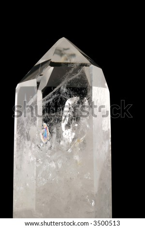 Quartz Crystal - black background - Strongly bound structure with fluid inclusions, trigonal symmetry and crystal faces well developed.  Light passes through its geologic intricacy.  Tectosilicate. - stock photo