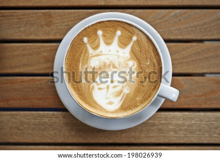 Queen latte art coffee cup on a wooden table - stock photo