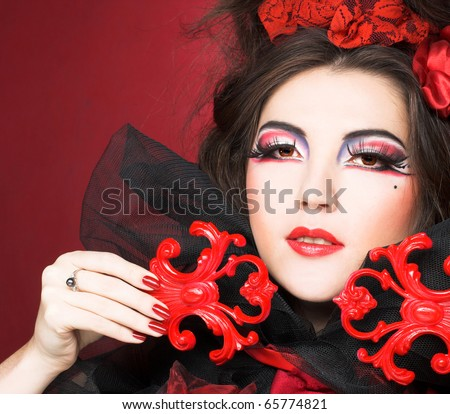 Queen of hearts. Creative lady in black and red colors and with bright make-up.
