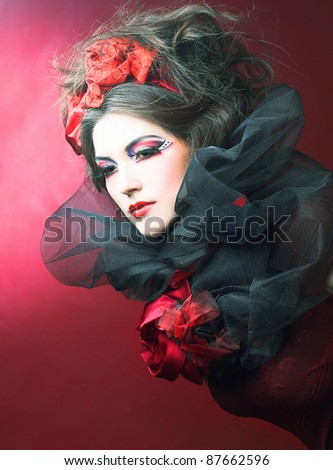 Queen of hearts. Creative lady in black and red colors and with bright make-up. - stock photo