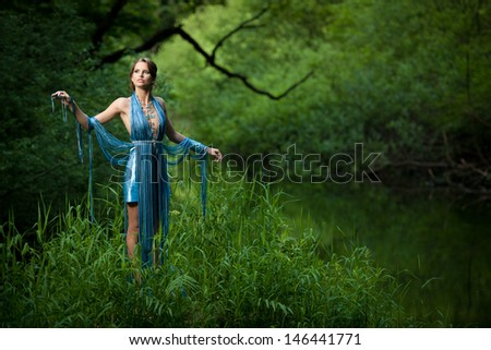 queen of swamp - attractive young woman in blue fashionable garment poses in forest wilderness