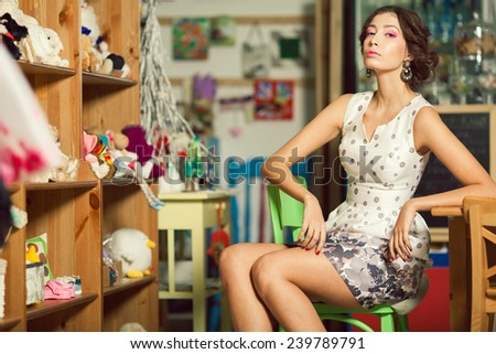 Queen of toys concept. Portrait of beautiful brunette with perfect make-up, hairdo, diamond earrings sitting in cafe with vintage decoration in white polka-dot dress. Many toys on shelves. Indoor shot - stock photo