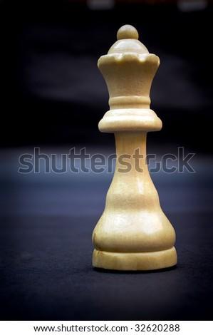 Queen, wooden chess piece on dark background. - stock photo