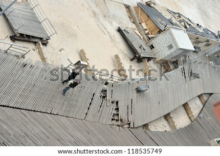 QUEENS, NY - NOVEMBER 11: Damaged boardwalk and aftermath recovery in the Rockaway area due to impact from Hurricane Sandy in Queens, New York, U.S., on November 11, 2012. - stock photo