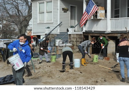 QUEENS, NY - NOVEMBER 11: Volunteers cleaning sand in the Rockaway Beach residential area  after Hurricane Sandy in Queens, New York, U.S., on November 11, 2012. - stock photo
