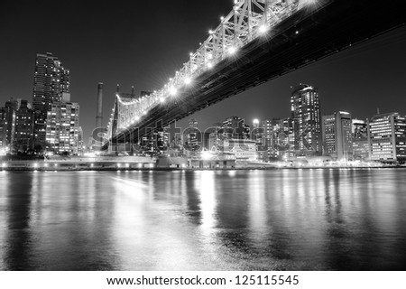 Queensboro Bridge over New York City East River black and white at night with river reflections and midtown Manhattan skyline illuminated. - stock photo