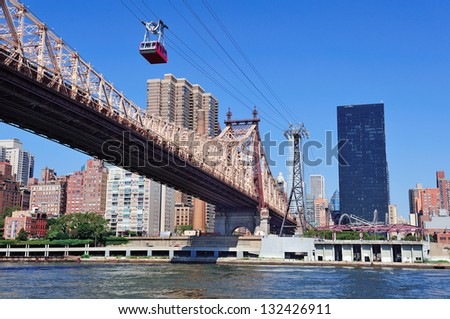Queensborough Bridge in Midtown Manhattan with New York City skyline over East River as the famous landmarks viewed from Brooklyn. - stock photo