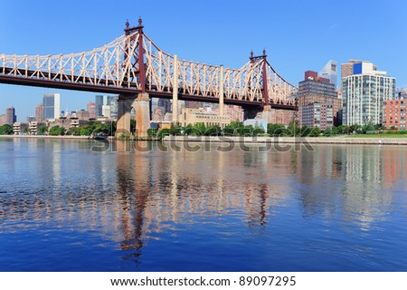 Queensborough Bridge in Midtown Manhattan with New York City skyline over East River as the famous landmarks viewed from Brooklyn.