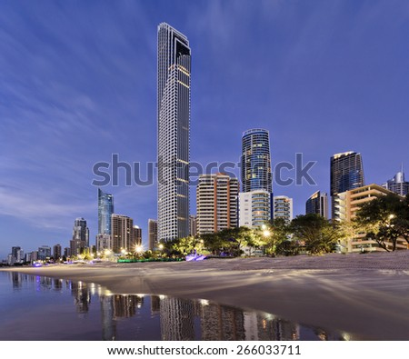 Queensland's gold coast landmark waterfront with tall modern skyscrapers reflecting in still beach waters at sunrise - stock photo
