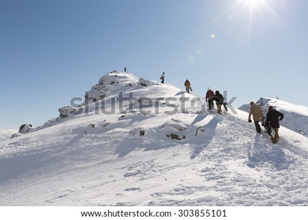 QUEENSTOWN, NEW ZEALAND - AUGUST 6: Unidentified skiers and snowboarders hike on the top of The Remarkables Ski Area on August 6, 2015 in Queenstown, South Island, New Zealand - stock photo
