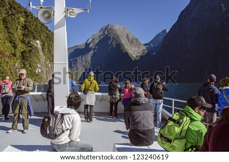 QUEENSTOWN, NEW ZEALAND - DECEMBER 27: Tourists enjoy a scenic cruise on Milford Sound in Fiordland on December 27, 2012 in Milford Sound, New Zealand. Fiordland features spectacular alpine scenery. - stock photo