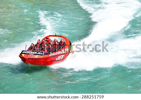 QUEENSTOWN, NEW ZEALAND - November 18: Tourists enjoy a high-speed boat ride on Queenstown's Shotover river on November 18, 2014 in Queenstown, New Zealand. - stock photo