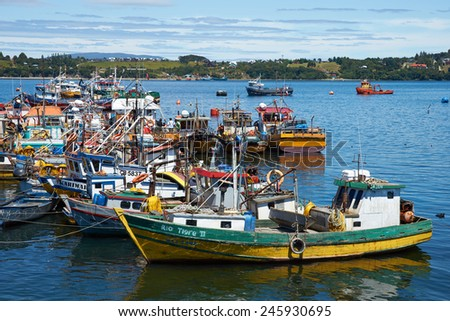 QUELLON, CHILE - JANUARY 15, 2015: Colourful fishing boats crowding the fishing port of Quellon on the island of Chiloe in Chile - stock photo