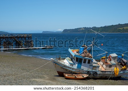 QUEMCHI, CHILE - JANUARY 14, 2015: Colourful fishing boat resting on the shore in Quemchi on the Island of Chiloe in Chile. - stock photo