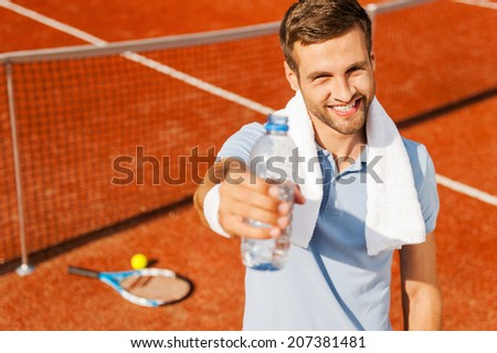 Quench your thirst! Happy young man in polo shirt and towel on shoulders stretching out bottle with water while standing on tennis court  - stock photo