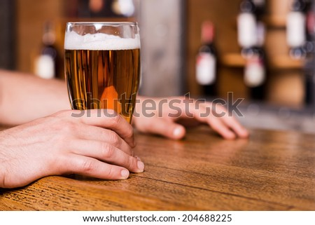 Quenching his thirst. Close-up of man holding glass with beer while standing at the bar counter