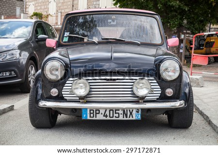 Quenza, France - July 1, 2015: Black Mini cooper car stands parked, closeup photo, front view