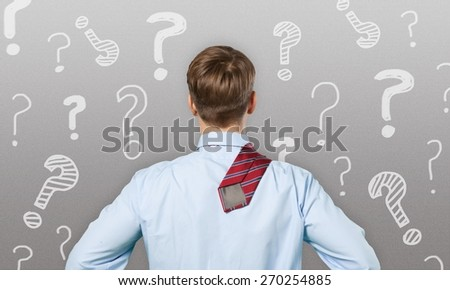 Question. Confused, young businessman looking at many chalk drawn question marks - stock photo