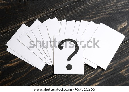 Question mark heap on table concept for confusion, question or solution on wooden background in the middle - stock photo