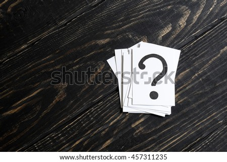 Question mark heap on table concept for confusion, question or solution on wooden background on the right - stock photo