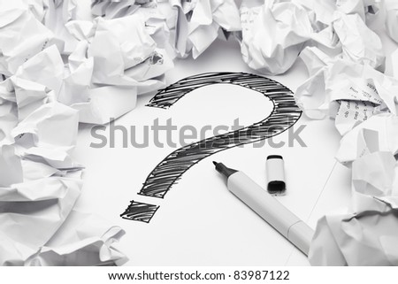 Question mark in the middle if crumpled papers - lack of inspiration concept - stock photo