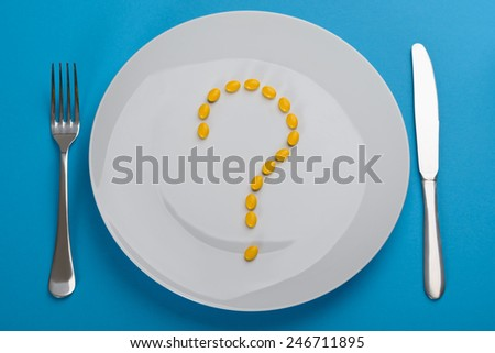 Question Mark Made From Pills In Plate On Blue Background - stock photo