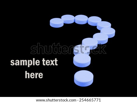 Question mark of tablets isolated on black background - stock photo