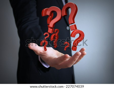 question marks over businessman hand