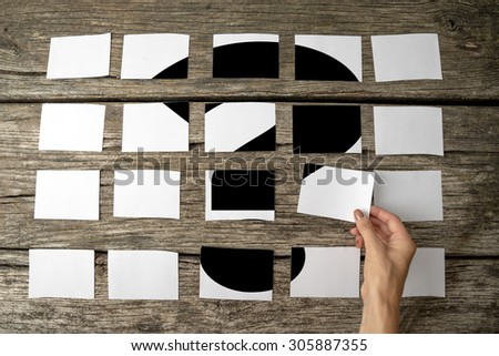 Question or query - solution or answer concept with a woman laying out rows of memo notes with a question mark and placing the last piece in place on the wooden background, close up of her hand. - stock photo