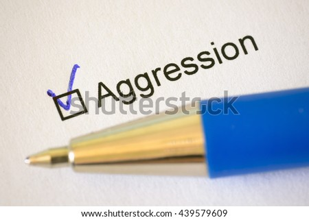 Questionnaire - blue pen and the inscription AGGRESSION with check mark on the white paper