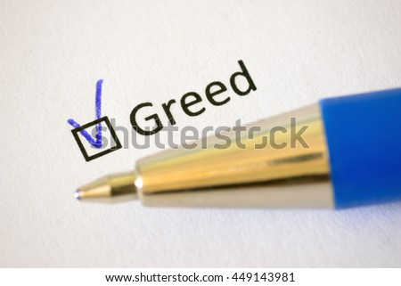 Questionnaire. Blue pen and the inscription GREED with check mark on the white paper - stock photo